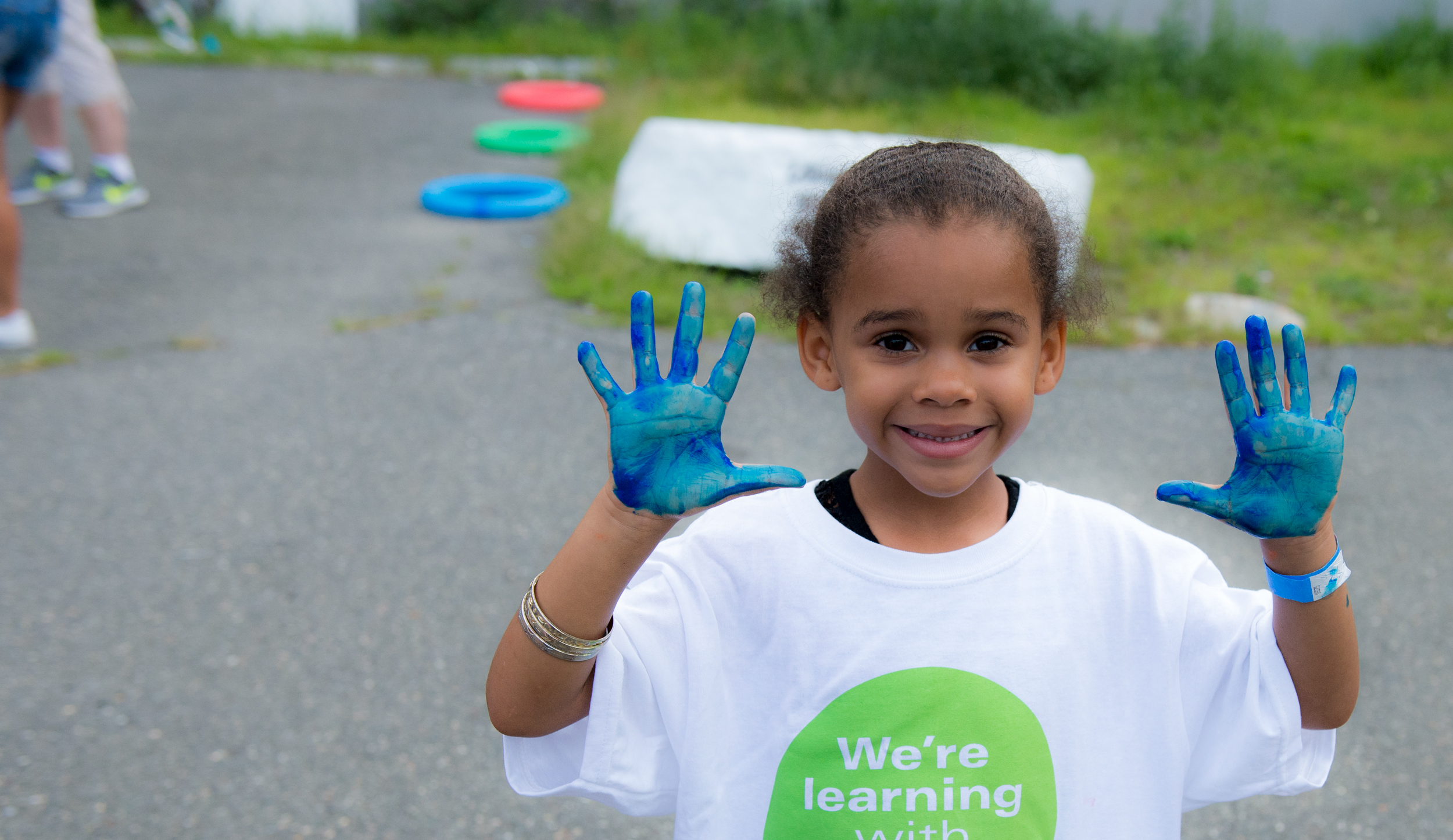 Child raising there hand to show that it is covered in blue paint
